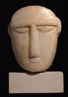 stela; Ancient South Arabian; 3rdC BC-2ndC BC; Yemen; Aden Protectorate. Conventionalized face from a stone funerary stela; back of head and neck unmodelled; eyes, ears and brows marked by rocked tool in low relief; eyebrows recessed for inlays.