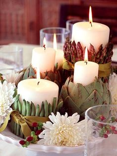 Other than elements from the outdoors, consider using fruits or vegetables in your Thanksgiving display.  This grouping of candles are surrounded with string beans, artichokes, and asparagus, then tied together with a satin ribbon