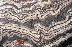 """Ptygmatic folding: """"At a small scale (outcrop-sized), contorted folds are found in metamorphic rocks such as gneisses. The rocks actually soften as they are heated during deep burial."""" Caption from link"""