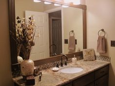 Our just remodeled bathroom using Rustoleum Cabinet Restorations, framing the ugly flat mirror by gluing frame to it, new granite counter top, sink, and fixtures.