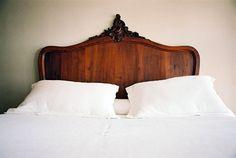 Angular, dark wood head board and crisp, white bedding.