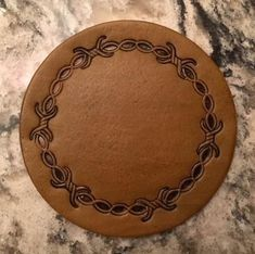"Hand Tooled Leather Coaster Set - Barb Wire Design - includes 4 coasters and 1 coaster holder. Made with high quality leather and suede. Every step is done by hand. Each coaster measures 3 3/4"" round. Each piece of leather has its own characteristics such as grain, color, density, thickness, and maybe a marking or brand."