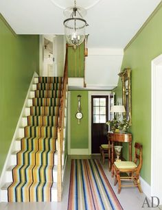 fun color for a foyer ~ Striped runners by Woodard & Greenstein animate the entrance hall, which is lit with an antique lantern; the early-19th-century tiger-maple demilune table and chairs were chosen because they match the banister, and the gilt-wood mirror is antique American.
