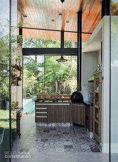 Atrás da cozinha, este charmoso espaço remete à mineirice de dois dos moradores. No piso, o porcelanato da Portobello imita ladrilho hidráulico. Sob o telhado de uma água, com inclinação de 8% e forro de cedro envernizado, o pé-direito varia de 3 a 4,50 m.