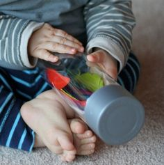 Discovery Bottles: VOSS water bottles (fancy store bought water) + objects +/_- water, baby oil, hair gel...this one is multi-colored feathers without any liquid...hot glue lid to bottle...include older kids by saying all the water has to be drunk before they can make the bottle(meaning with one kid you're gonna be making about one bottle a day) and let them present the bottle to the baby