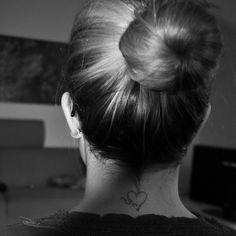Pequeño tatuaje en la nuca de las iniciales de sus seres queridos envueltos por un corazón.