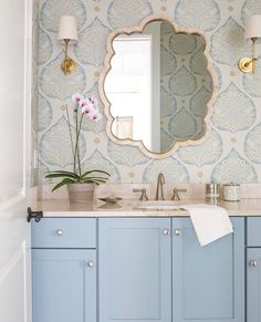 Powder room with overscale paisley paper, trefoil mirror, pale blue vanity, brass sconces