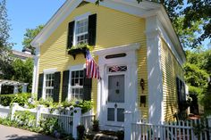 White door with white screen on yellow house with white trim and black accents.