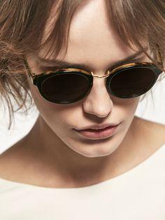 Gafas de sol estilo round con montura de pasta negra e interior efecto carey, lentes con filtro de protección UV de la clase III y detalle de puente metálico. Se acompañan con una funda protectora con el emblema grabado de la firma.