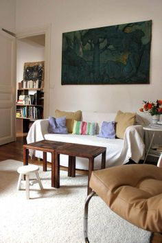sofa covered in blanket, pillows, stool, coffee table