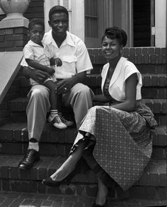 Portrait of baseball star Jackie Robinson w. his wife Rachel and their son Jackie Jr. sitting on front steps of their home in Brooklyn.  July 1949