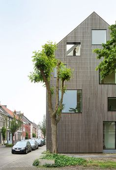 Square windows puncture the timber facade of this townhouse in Ghent, Belgium, which local studio FELT Architecture recently refurbished