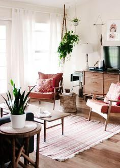 Love this midcentury modern living room with vintage peg leg coffee table and arm chairs, white ceramic accents, pretty pink upholstery, and tons of hanging plants in macrame hangers!
