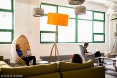 Community workspace with rattan pendant lights, and a hanging chair