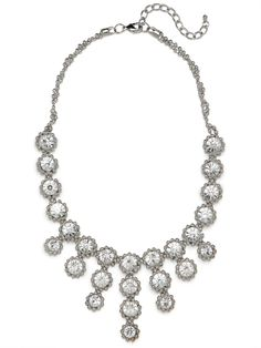Delight in the charming flower power of this striking statement necklace. It features a lavish array of oversized gems, framed by silver beads to floral effect, and cast in a pretty fringe silhouette.