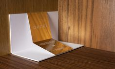 #SS2013 #MFW invitation for Gucci | Always good, and currently gold, Gucci's was a smooth white flip-up card propped up with a metallic band.