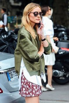 Olive jacket over white shirt with red print skirt.