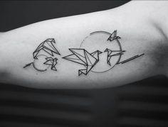 tatouage géométrique à l'intérieur du bras composé de grues en origami et deux soleils