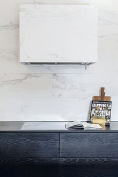 Kitchen details - extractor fan covered with marble like Italian ceramic tiles. Real marble do not tolerate acid, so this ceramic tile is optimal in the cooking area.