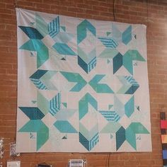 "I love hanging quilts on the brick walls of my shop it's the perfect backdrop!!! Especially for this quilt one of my soon-to-be released patterns ""Starcrossed"". Made with Blueberry Park fabric from @robertkaufman #quiltingismytherapy by angelafmq"
