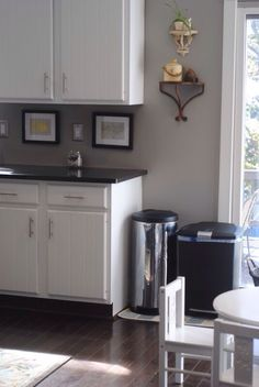 White cabinets, light gray walls, dark gray countertops, black & stainless steel appliances & furniture