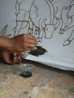 Filling the pattern of wax with paint, making batiks, Indonesia