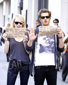 Emma Stone & Andrew Garfield hold up improvised signs for charity to paparazzi