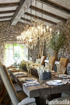 Designer Wendy Owen made the dining table on her Sonoma property from antique salvaged beams; she slipcovered the Ron Mann Design chairs in vintage burlap grain sacks. A grouping of five chandeliers illuminates the table.