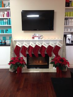 "A Dimplex 25"" Contemporary Electric Fireplace at The Salon of Fairfield, outfitted with Christmas stockings."