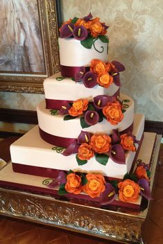 Four tier wedding cake with champagne colored fondant, burnt orange roses and plum calla lilies cascading down the tiers.