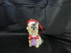 This adorable Christmas ornament features a Yorkie sporting Santas Hat and a Christmas Present. It is light weight, but a solid piece that is sure to