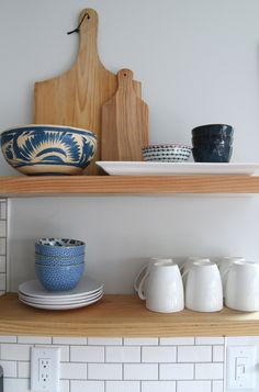 Make open kitchen shelving useful and beautiful with a few key items such as cutting boards and coffee mugs.