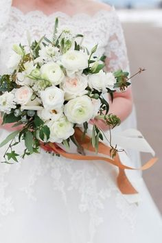 An all-white wedding bouquet from Frances Floral Design for the prettiest Colorado wedding. Beautiful white and blush roses, ranunculus and soft greenery complete this arrangement.