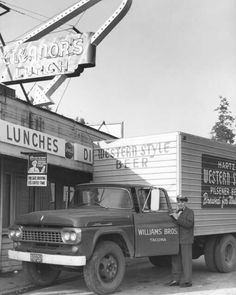 B.D. Lamb, driver for Williams Bros., stands next to his Ford truck outside of Eleanor's Restaurant on (Old) Hwy. 99 on February 2, 1961. Mr. Lamb has the driver's door open. There are large signs on the truck advertising Hartz Western Style Beer and Pilsener Beer.