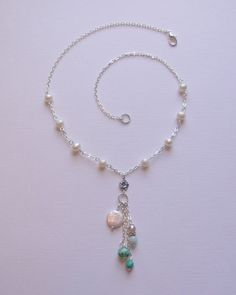 """The """"Sea Scape"""" necklace. A beautifully unique necklace in lovely hues. This necklace is made with freshwater pearls, agate, turquoise and Czech glass. It also has a tiny flower charm. It is has a very sweet look and is one of a kind. The chain is 18 inches long and the pendant hangs down about 3.5 inches. $35 including shipping www.blushingpixie.com"""