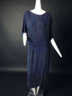 Gorgeous evening dress in navy silk crepe and adorned in a black seed bead design. The dress has a scoop neckline and falls straight to the elastic gathering below the waist. Attached sash ties at the