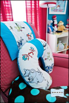 adorable red and white polka dot chair and the lamp beside it is red with a blue and white strip around the bottom