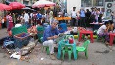 Anthony Bourdain reads the paper next to a local market in Yangon, Myanmar. Apparently, the people who usually eat there are dwarves.