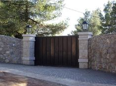 Stone wall topped with lights. Wooden driveway gate. No longer listed on the site