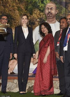 The Queen then posed with the woman alongside other officials at the 36th annual trade fai...