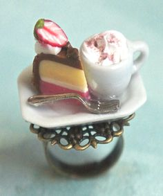 this ring features a slice of handmade neapolitan cake sculpted from polymer clay, along with a miniature cup coffee. both minis sits on a white ceramic plate that is securely attached to an adjustabl