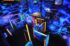Indoor laser tag arena. Multiple story and alien themed with fog and techno and trance music with black lights.