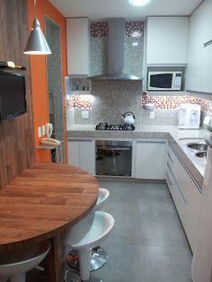 Cozinha com bancada em L e mesa em semi-círculo com painel