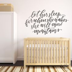 """""""Let her sleep for when she wakes she will move mountains"""" written in black vinyl as a wall decal placed on a light pink wall in a girls nursery behind a wooden crib. The decal is written in handwritten, chic lettering."""