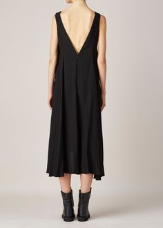 Sleeveless, draped A-line dress in black rayon blend. Low v-neck with draped fabric in back. Hidden zip closure at back. Side slit pockets. Dry clean.