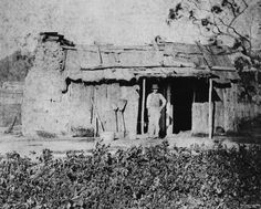 Rough bush dwelling, Stanthorpe ca. 1872 - Rough bush dwelling made of sawn timber with a stone chimney and some household brooms and water containers in front. A man stands at the front door.