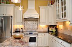 White cabinets, dark granite, stainless steel appliances, custom tile backslash, yellow kitchen ... by the BEST custom home builder / remodeler in central Florida | www.allinconstruction.com
