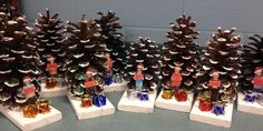"""These turned out sooooo much better than what I envisioned. I'm so pleased. A parent donated big pine cones. I hot glued them onto 1x4s and the kids decorated them with glitter. I took pics of my students, printed and laminated them. I then glued them along with some mini ornaments from the Dollar Tree. The kids don't know their pics are in front of the """"tree"""". Hehe. They will be so proud to give these keepsakes."""