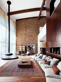 Leather wall paneling and stone wall designs, combined with contemporary fireplace, embroidered cushions and large wool rug, modern living room design with ethnic charm