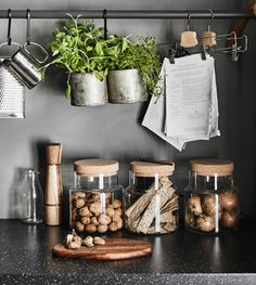A granite effect worktop with glass storage jars holding nuts, onions and crispbreads
